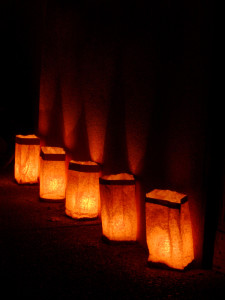 Five luminarias lined up on a sidewalk on Christmas Eve in New Mexico.